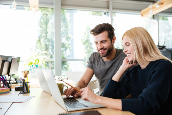 happy-young-colleagues-sitting-office-coworking-using-laptop_171337-17668.jpg